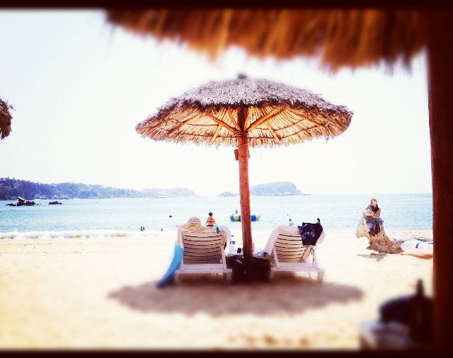 Shade under a beach umbrella with a view of the ocean in Huatulco, Mexico.