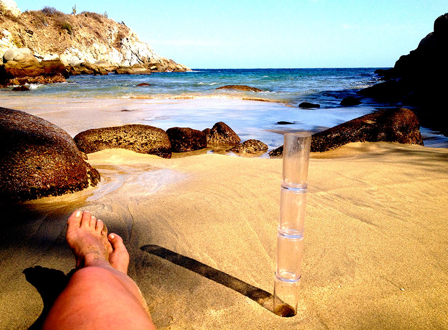 Appreciating nature with stacked, empty cocktail glasses on the beach.